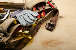 Tool belt with carpenter tools and protective wear on plywood sheet